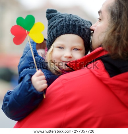 Father and daughter with a flag on Lithuanian independence day - stock photo