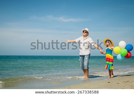 Father and daughter with balloons playing on the beach at the day time. Concept of friendly family.