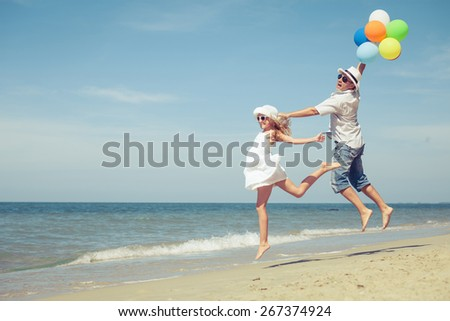 Father and daughter with balloons playing on the beach at the day time. Concept of friendly family. - stock photo