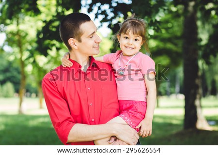 father and daughter.Young man and beautiful little girl in summer park