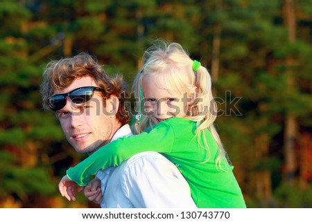 Father and daughter.Young man holding blonde little girl on shoulders in park - stock photo