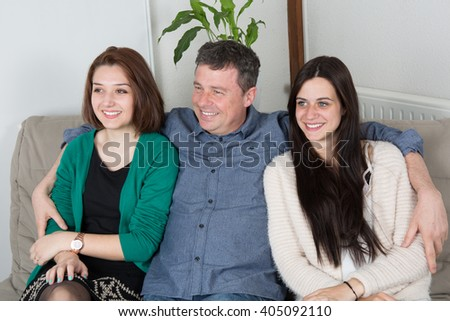 Father and daughters on sofa at home sharing time
