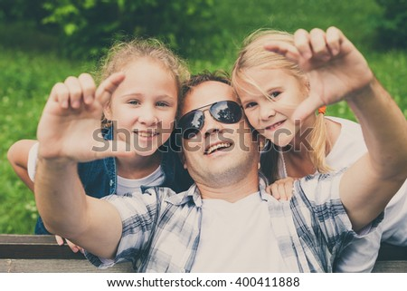 Father and daughters  playing at the park at the day time. Concept of friendly family.