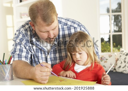 Father and Downs Syndrome daughter drawing - stock photo