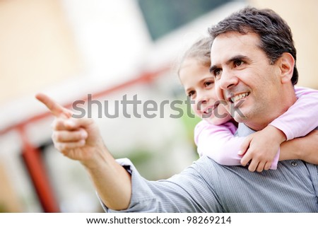 Father and girl pointing away and smiling - outdoors - stock photo