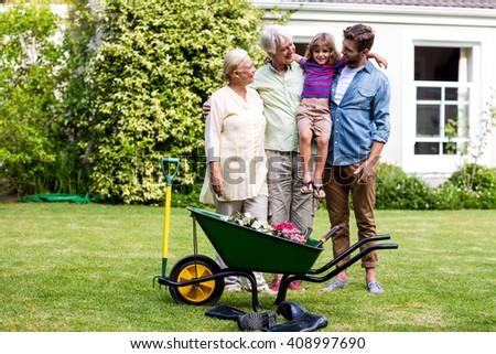 Father and grandfather standing with granny carrying son at yard - stock photo