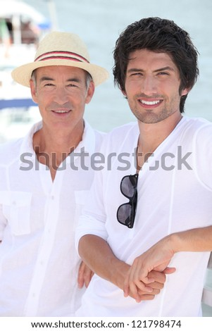 Father and grownup son enjoying the sunshine - stock photo