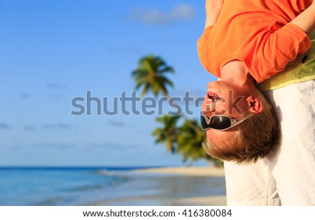 father and happy little son playing on beach - stock photo