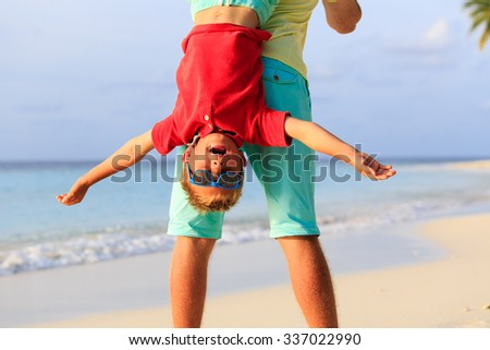 father and happy little son playing on summer beach - stock photo