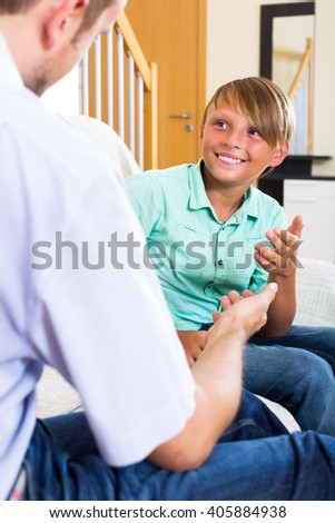 Father and happy teenage son discussing something interesting indoors - stock photo