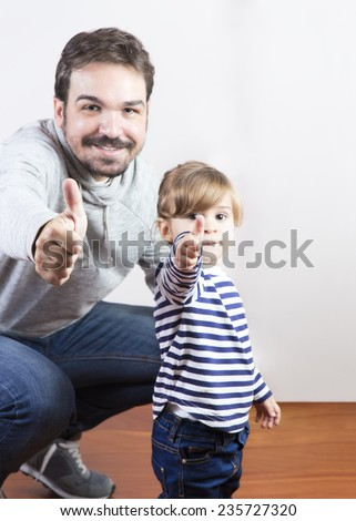 Father and her little daughter with thumbs up. Adult man and baby girl are happy and with great rapport - stock photo