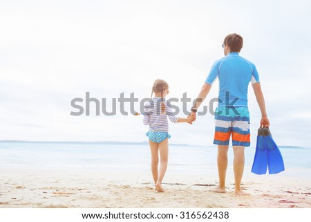 Father and his adorable little daughter at beach - stock photo