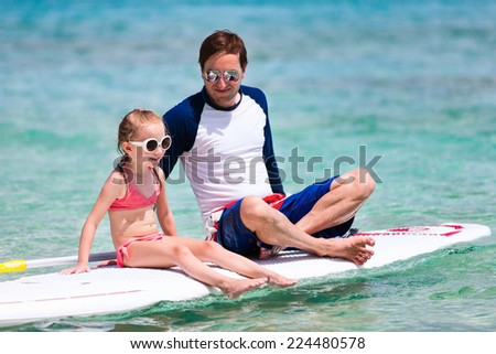 Father and his adorable little daughter sitting on stand up board having fun during summer beach vacation - stock photo