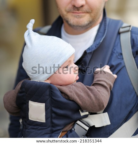 Father and his baby boy in a baby carrier, outdoors portrait - stock photo