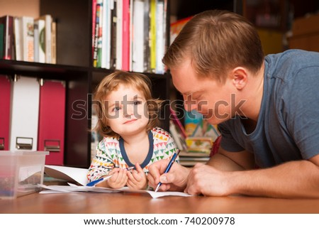 father and his baby daughter drawing togetherness. The happy family spends time together at home.