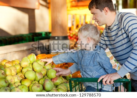 father and his cheerful son choosing fruits at the market - stock photo