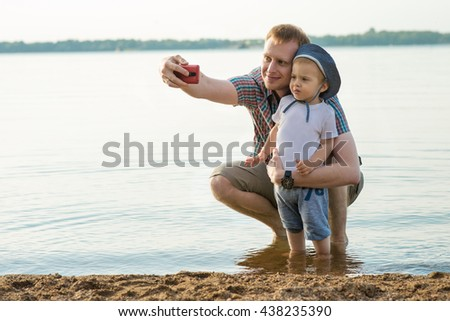 Father and his child are taking self-ie by mobile on the beach, summertime