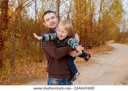 Father and his child have fun outdoor on sunny autumn day - stock photo