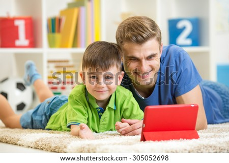 father and his child son play with tablet pc - stock photo