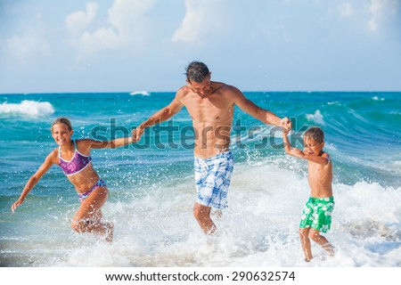 Father and his children playing and running on the beach. Concept of friendly family.
