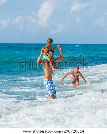 Father and his children playing in wave in the sea. Concept of friendly family.