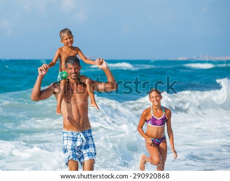 Father and his children playing in wave in the sea. Concept of friendly family. - stock photo