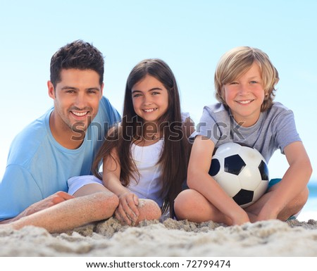 Father and his children with a ball - stock photo