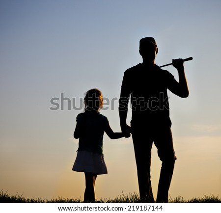 Father and his daughter playing golf at sunset - stock photo