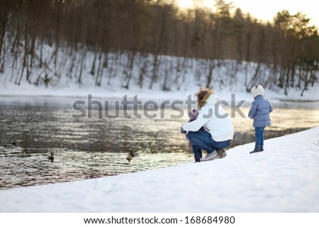 Father and his daughters feeding ducks at winter - stock photo