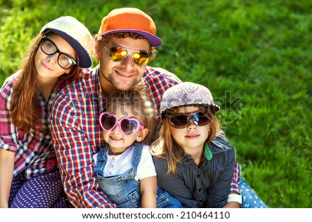 Father and his 3 daughters lie on the grass in sunglasses happy.  - stock photo
