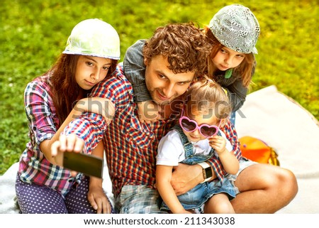 Father and his 3 daughters lie on the grass in sunglasses happy. Taking selfie by mobile phone - stock photo