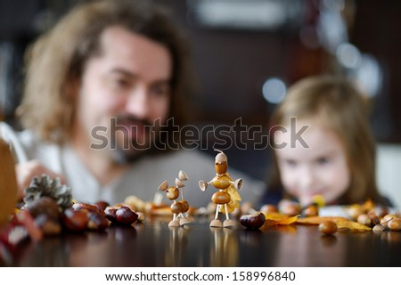 Father and his kid making chestnuts creatures together - stock photo