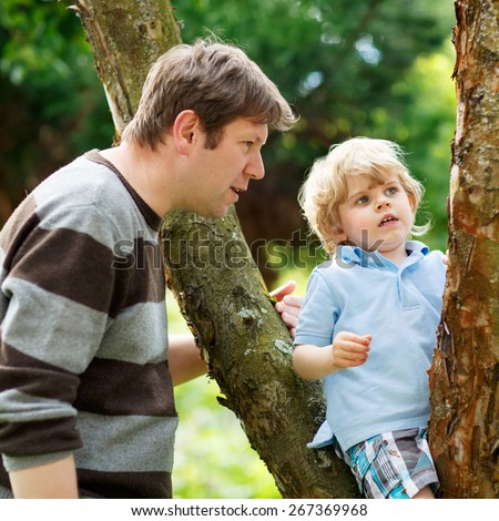Father and his little cute son having fun in forest. Funny kid boy climbing on tree. Family leisure outdoors, on warm summer day. - stock photo