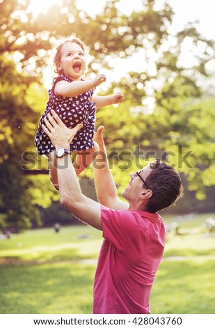 Father and his little daughter having fun in park - stock photo