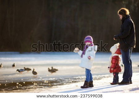 Father and his little daughters feeding ducks at winter - stock photo