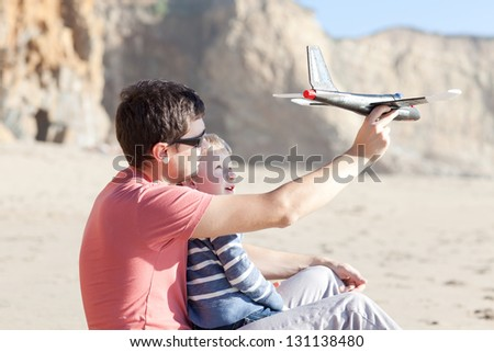 father and his little son playing with toy plane together - stock photo