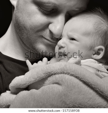 Father and his newborn baby. MANY OTHER PHOTOS FROM THIS SERIES IN MY PORTFOLIO. - stock photo