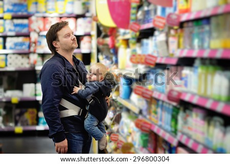 Father and his son at supermarket  - stock photo
