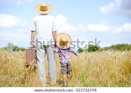 Father and his son in straw hats travelling on summer wheat field. Man carrying a heavy suitcase and holding child's hand. They both are looking in the distance. The sun is shining. - stock photo