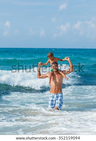Father and his son playing in wave in the sea. Concept of friendly family. - stock photo