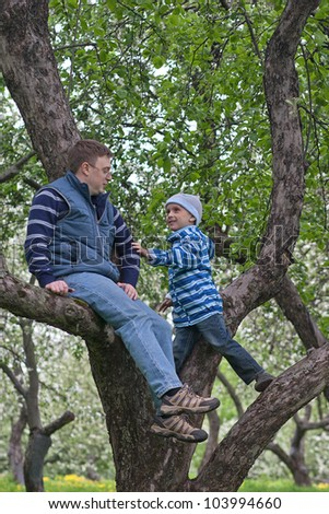 Father and his son playing on an apple tree - stock photo