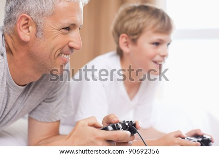 Father and his son playing video games in a bedroom - stock photo