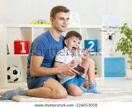 Father and his son playing with RC helicopter toy - stock photo