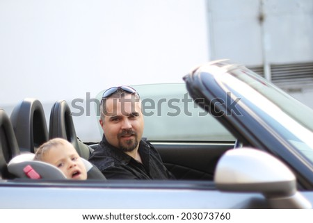 Father and his son strapped in the child seat in cabriolet  - stock photo