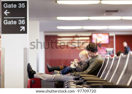 father and his son waiting and playing at the airport - stock photo