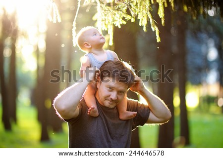 Father and his son walking at summer park - stock photo