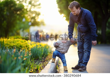 Father and his son walking at summer park