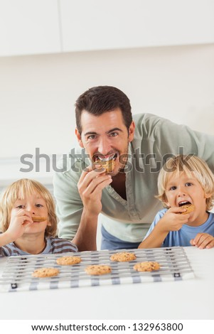 Father and his sons eating cookies in the kitchen