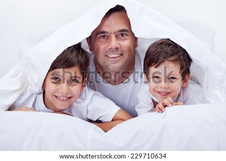 Father and his sons spending some lazy time together having fun - stock photo