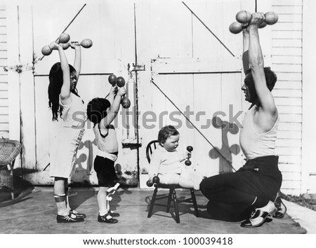Father and his three children having a workout with dumbbells - stock photo